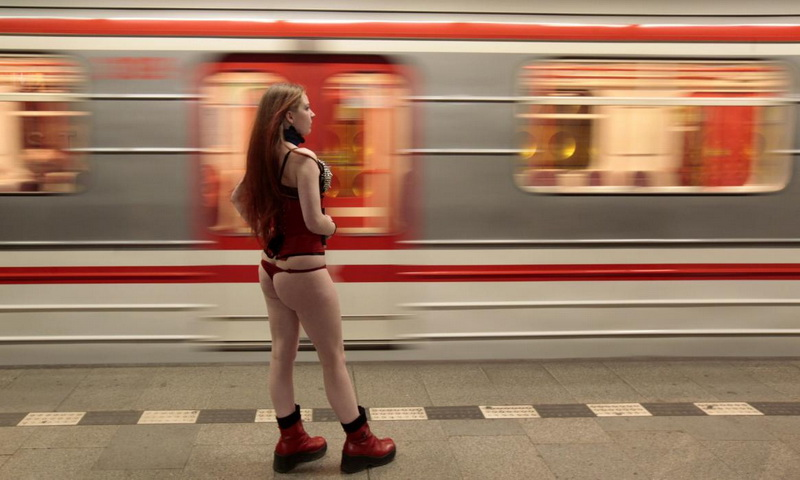 "A passenger not wearing pants waits for a subway train during the ""No Pants Subway Ride"" in Prague"