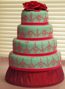Four tier wedding cake with henna pattern and red flower topper