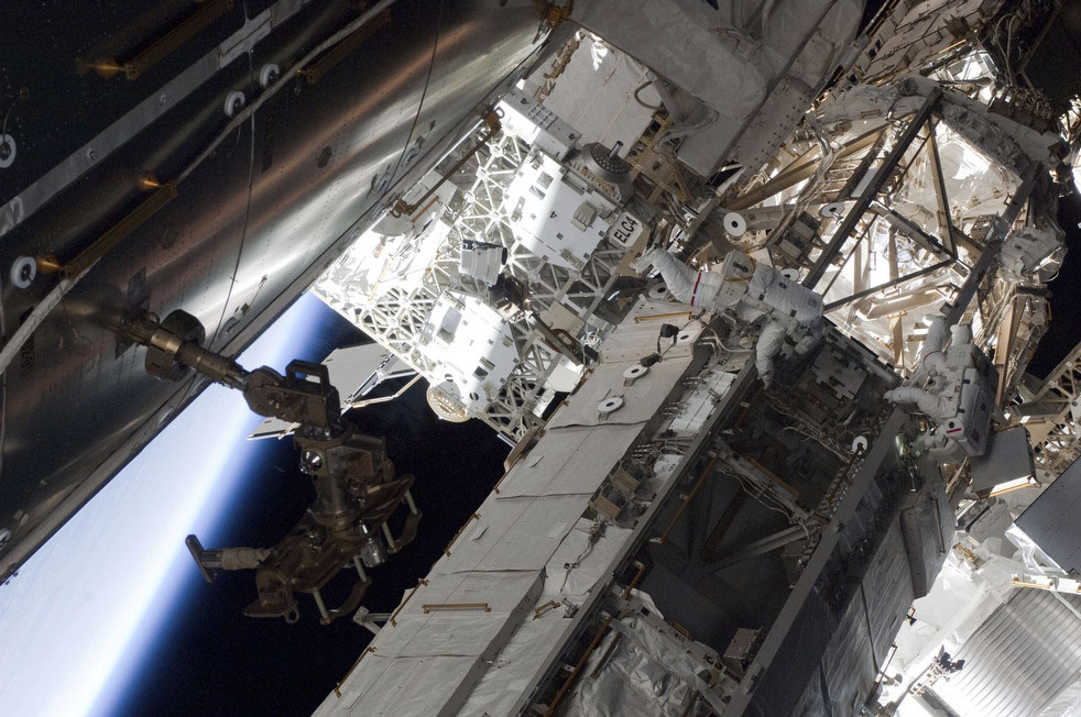 NASA astronauts Andrew Feustel (right) and Greg Chamitoff, both STS-134 mission specialists, participate in the mission's first session of extravehicular activity (EVA) as construction and maintenance continue on the International Space Station. During the six-hour, 19-minute spacewalk, Feustel and Chamitoff retrieved long-duration materials exposure experiments and installed another, installed a light on one of the station's rail line handcarts, made preparations for adding ammonia to a cooling loop and installed an antenna for the External Wireless Communication system.