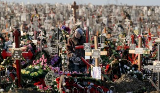 A woman stands by the grave of her relative in the Saint Lazarus cemetery in Chisinau, Moldova, Saturday, Jan. 30, 2016. The Saint Lazarus cemetery is one of the largest in Europe with a surface of  2 million square meters and more than 300 thousand graves and is considered one of the top places to visit in the Moldovan capital. (AP Photo/Vadim Ghirda)